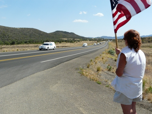 Courtesy of Kathy Montgomery |The second is our communications director Frances Lechner, holding the flag. She stayed with us during the evacuation. We had driven out to Highway 89 to watch the procession of hearses pass by.